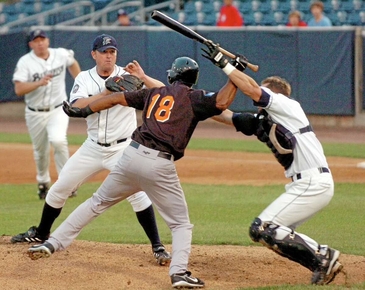 In this Aug. 14, 2007 file photo, Bridgeport Bluefish catcher John Nathans, right, tries to prevent Long Island Ducks batter Jose Offerman from hitting pitcher Matt Beech with a bat during a fight in the first inning of an Atlantic League game in Bridgeport.