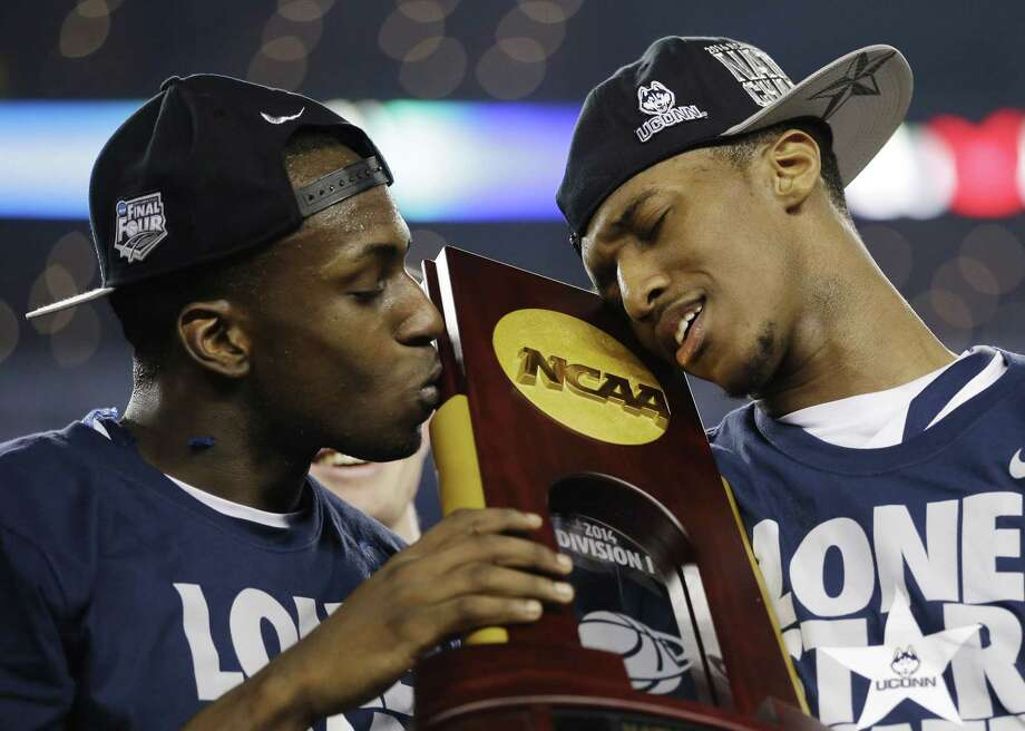 UConn guards Terrence Samuel, left, and Ryan Boatright hold the national championship trophy after beating Kentucky 60-54 on April 7 in Arlington, Texas. Photo: David J. Phillip — The Associated Press File Photo  / AP
