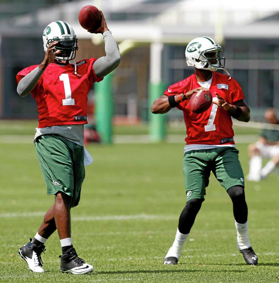 This June 4 file photo shows New York Jets quarterbacks Michael Vick, left, and Geno Smith working out during an OTAs in Florham Park, N.J. Photo: Julio Cortez — The Associated Press File Photo  / AP