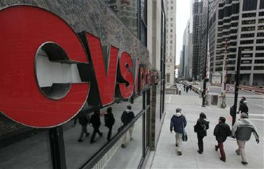 Pedestrians walk pass a CVS store in Chicago. Photo: AP / AP