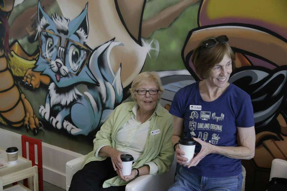 In this photo taken Thursday, Nov. 6, 2014, Jo Anne Driscoll, left, and Peggy Harding, right, watch others play with cats at the Cat Town Cafe in Oakland, Calif. Similar to cafe concepts in Asia & Europe, the care has become America's first permanent feline-friendly coffee shop. Cafe customers pay to pet cute kitties while sipping on tea or expresso drinks. It allows customers, who may not be able to have cats in their own homes, to enjoy the benefits of furry friends for short times without the responsibility. The animals come from a partnership with a local animal shelter and are also available for adoption. This may just be the beginning of this country's cat cafe craze as others plan on opening soon in Seattle, Portland, San Diego and Denver. (AP Photo/Eric Risberg) Photo: AP / AP