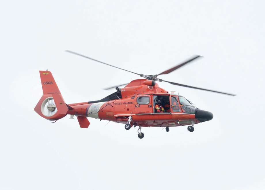 A U.S. Coast Guard helicopter flies over Santa Rosa Sound near Navarre, Fla., Wednesday, March 11, 2015.  A fire official says divers are still trying to recover a flight recorder from the site of a helicopter crash that killed seven Marines and four soldiers. Mark Giuliano, the fire chief at Eglin Air Force Base, said Thursday that the Black Hawk helicopter was still in about 25 feet of water.   (AP Photo/Northwest Florida Daily News, Devon Ravine) Photo: AP / NORTHWEST FLORIDA DAILY NEWS