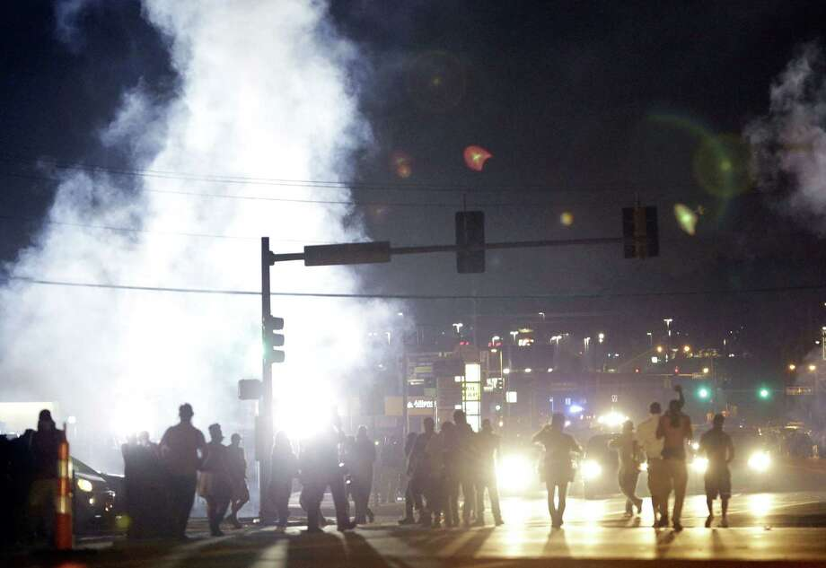 FILE - In this Monday, Aug. 18, 2014 file photo, people stand near a cloud of tear gas in Ferguson, Mo. during protests for the Aug. 9 shooting of unarmed black 18-year-old Michael Brown by a white police officer. The U.S. government agreed to a police request to shut down several miles of airspace surrounding Ferguson, even though authorities said their purpose was to keep media helicopters away during protests in August, according to recordings of air traffic control conversations obtained by The Associated Press. (AP Photo/Jeff Roberson) Photo: AP / AP