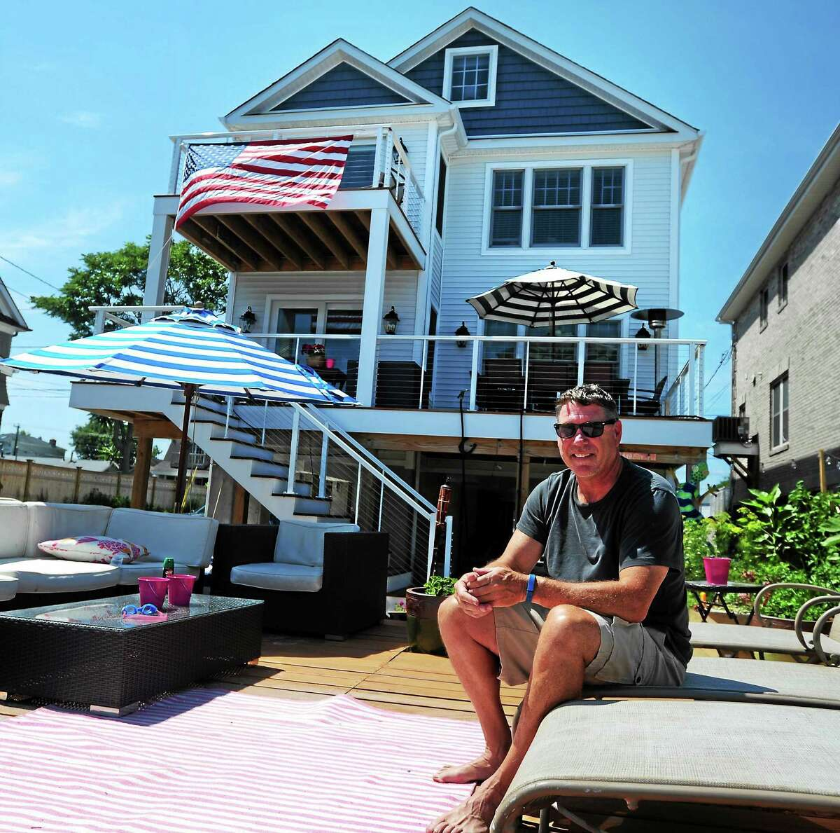John McNamara sits in front of his home by Bethel-based Westchester Modular Homes, on July 10, 2015 in Fairfield, Conn. Since the state accepted their application to the program, Westchester Modular Homes has finished more than a dozen homes for victims of the Superstorm Sandy.