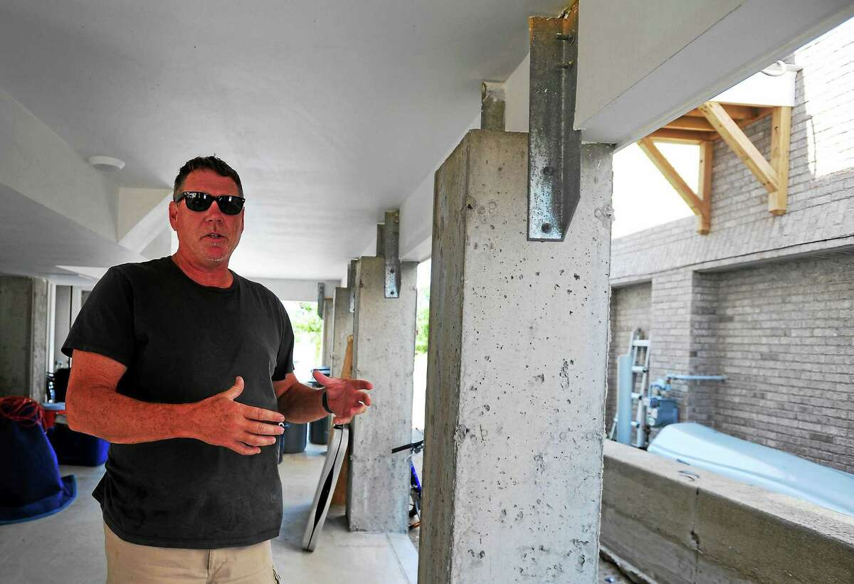 Homeowner John McNamara, stands near the concrete pilings on his waterfront house in Fairfield, Conn., on July 10, 2015. Since the state accepted their application to the program, Westchester Modular Homes has finished more than a dozen homes for victims of the Superstorm Sandy.