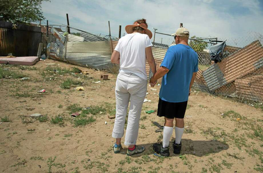 Concerned citizens observe a moment of silence, Monday, July 21, 2014 in the field where two homeless men were bludgeoned to death by teenagers over the weekend near in Albuquerque, N.M. (AP Photo/Albuquerque Journal, Roberto E. Rosales) Photo: AP / Albuquerque Journal