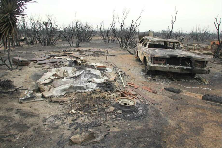 A burned-out car is seen on July 18, 2015 in the rural community of Baldy Mesa, Calif. A wildfire swept across Interstate 15 on Friday, destroying over a dozen vehicles before burning several homes in the community of Baldy Mesa. Photo: AP Photo/Matt Hartman  / FRE171313AP