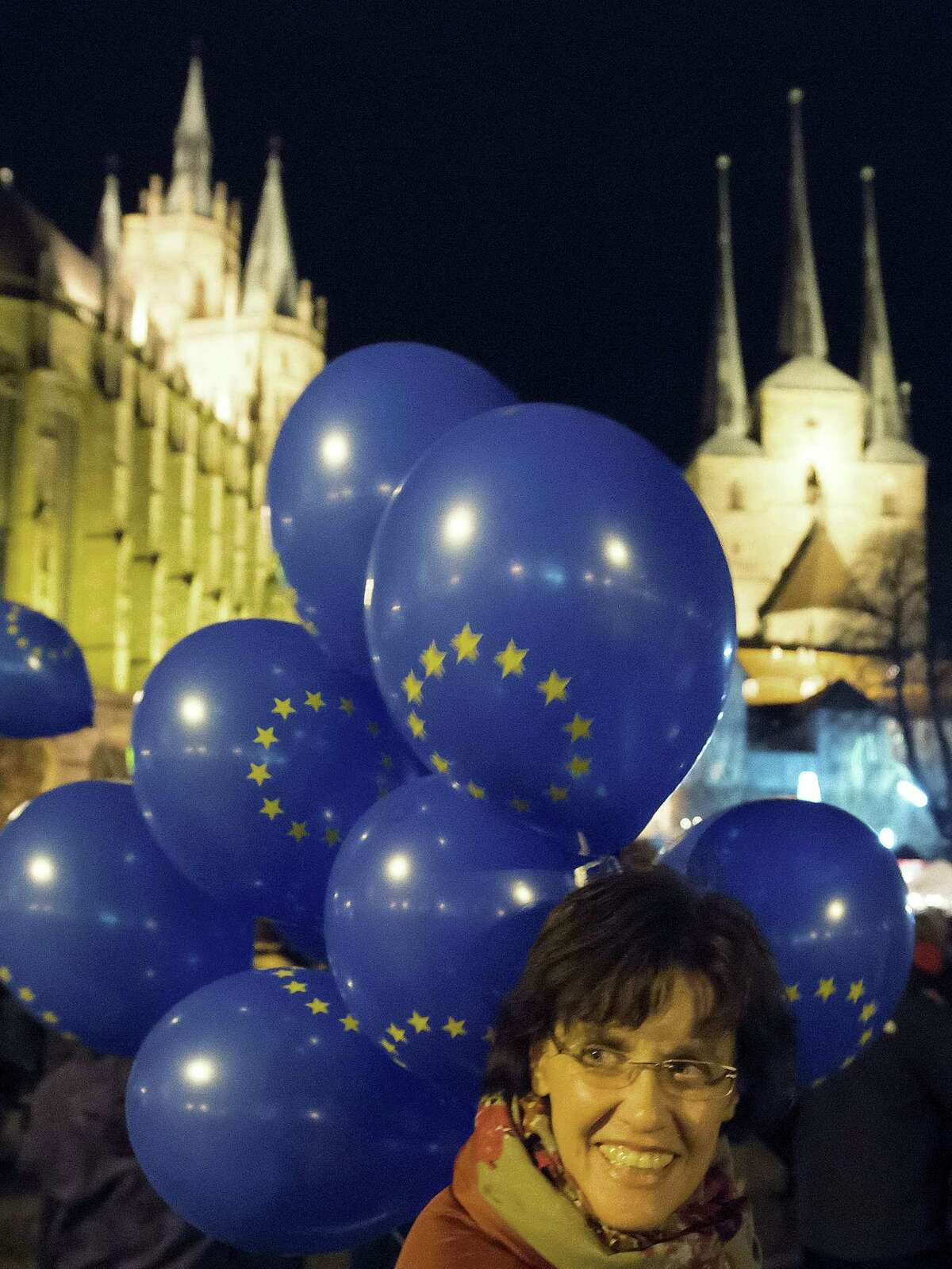 A woman stands in front of balloons with an EU logo as thousands of people demonstrate during a rally of the Alliance for democracy, diversity and human solidarity in Erfurt, central Germany, Monday, Nov. 9, 2015. They demand a better integration of migrants in Germany and condemn any kind of violence.