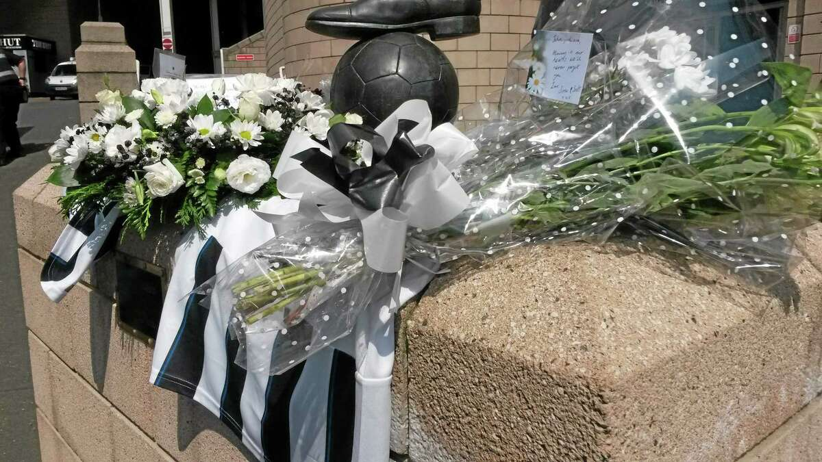 Flowers and football shirts are laid around the Sir Bobby Robson statue outside St James Park the home of Newcastle United soccer team in Newcastle England Friday July 18, 2014, after two fans of the club died on board flight MH17 which was shot down over the Ukraine on Thursday. John Alder, in his 60s, and Liam Sweeney, 28, were travelling to New Zealand to watch Newcastle play in a pre-season tour. (AP Photo/Tom White/PA) UNITED KINGDOM OUT NO SALES NO ARCHIVE