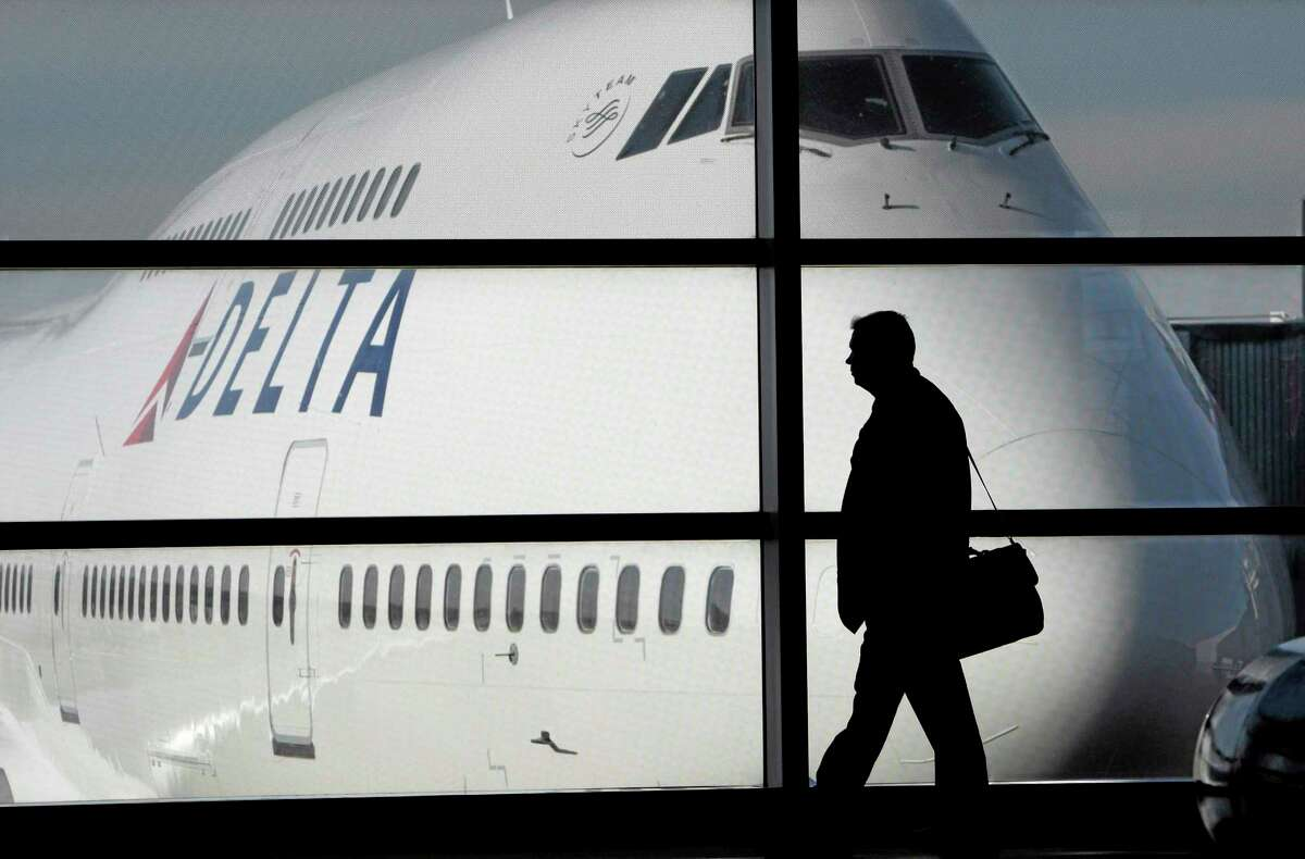 FILE - In this file photo made Jan. 21, 2010, a passenger walks past a Delta Airlines 747 aircraft in McNamara Terminal at Detroit Metropolitan Wayne County Airport in Romulus, Mich. Delta Air Lines on Tuesday, July 22, 2014 canceled all flights to Israel until further notice, citing reports that a rocket landed near Tel Aviv's Ben Gurion Airport. (AP Photo/Paul Sancya, File)