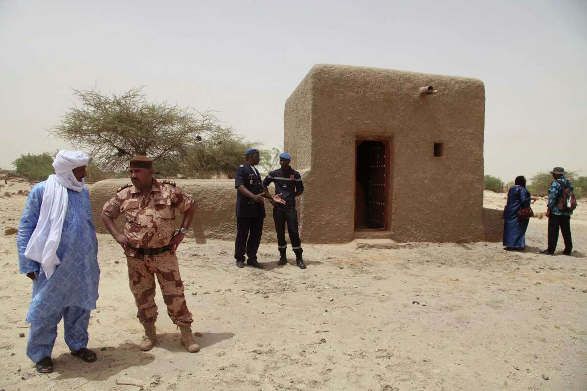 In this photo taken July 18, 2015, people attending a ceremony stand near a mausoleum, right, that was restored in Timbuktu, Mali. The 14 mausoleums in Maliís northern Timbuktu that had been destroyed by Islamic extremists years ago have been restored.