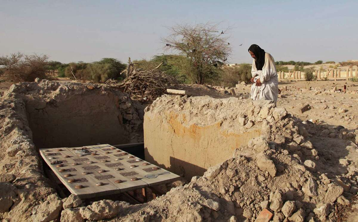 In this Friday April 4, 2014 photo, Mohamed Maouloud Ould Mohamed, caretaker of the tombs at Timbuktuís mausoleums, prays at a damaged tomb in Timbuktu, Mali.