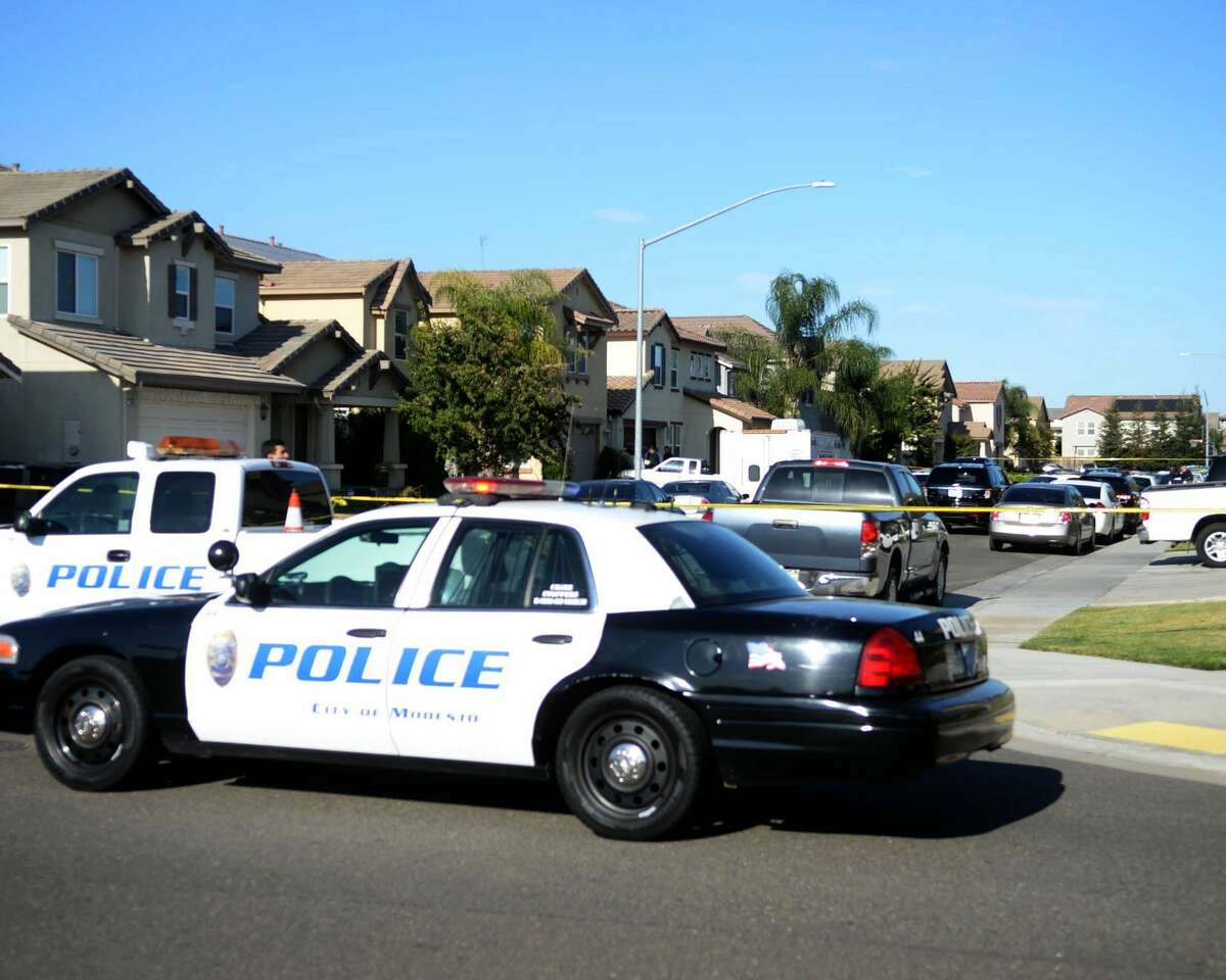 Modesto Police block a road near a home where five people were found dead on July 18, 2015 in Modesto, Calif. A Modesto police spokeswoman said officers responding to a request to conduct a welfare check discovered the bodies of three children and two adults Saturday afternoon.