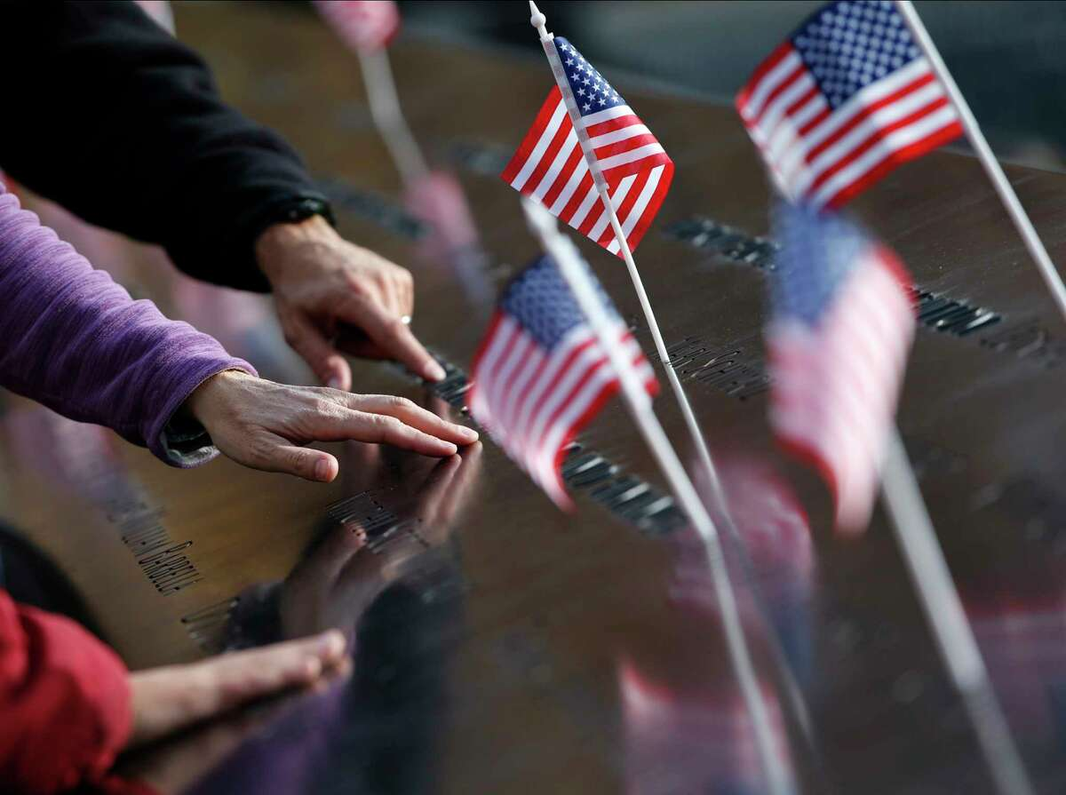 Hands reach out to touch the names inscribed at the South Pool of the 9/11 Memorial at the National September 11 Memorial & Museum, Monday, Nov. 9, 2015, in New York, following a ceremony honoring first responders who were also military veterans. The ceremony was held in advance of Veterans Day.