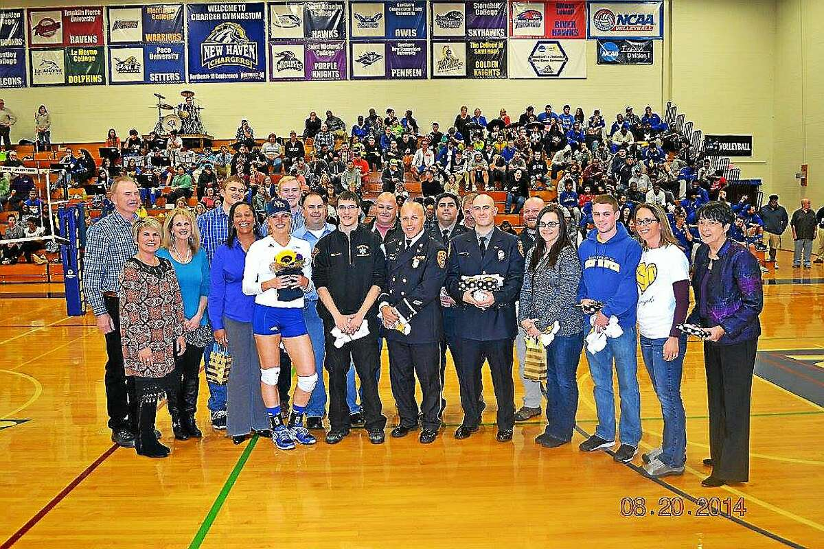 """Courtesy University of New Haven Women's Volleyball Ashley Dalton stands with """"Ashley's Angels,"""" the first responders who helped save her life on August 30 when she collapsed in Middletown."""