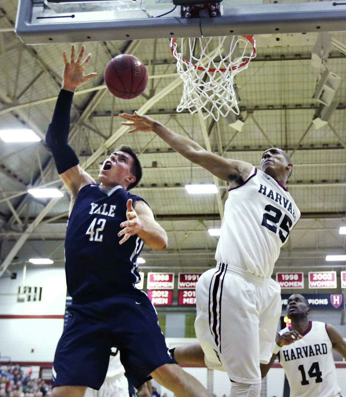 Harvard center Kenyatta Smith (25) blocks a shot by Yale's Matt Townsend during the first half of their game on March 6.