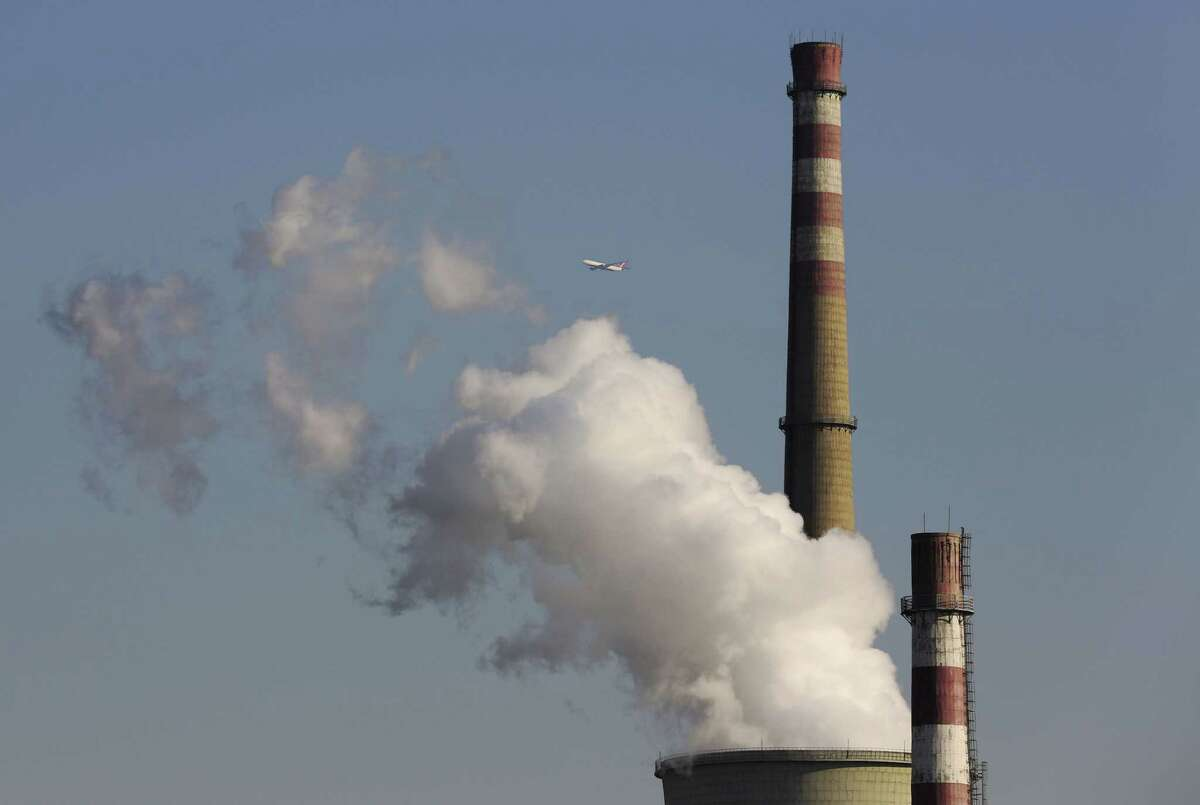 A passenger airliner flies past smokes emitted from a coal-fired power plant in Beijing, China.