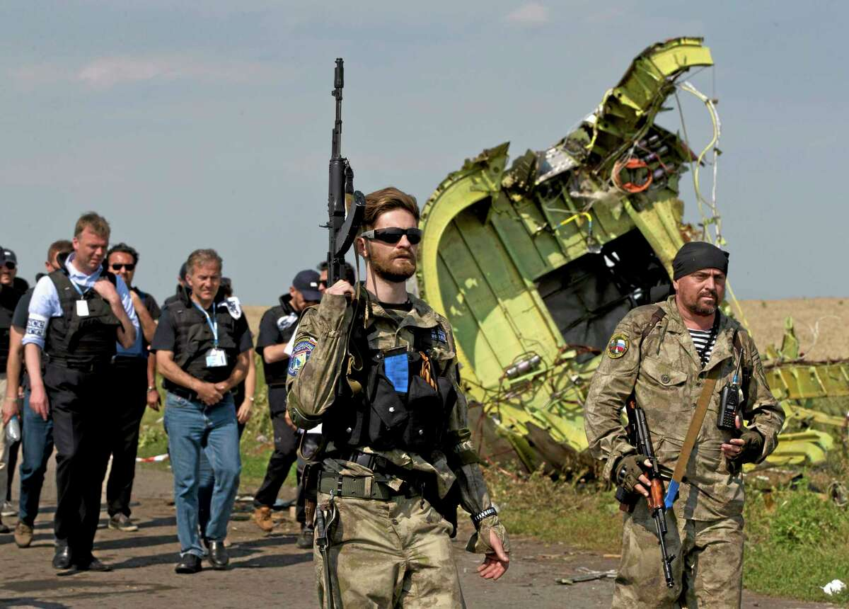 Pro-Russian rebels, right, followed by members of the OSCE mission, walk by plane wreckage as they arrive for a media briefing at the crash site of Malaysia Airlines Flight 17, near the village of Hrabove, eastern Ukraine, Tuesday, July 22, 2014. A team of Malaysian investigators visited the site along with members of the OSCE mission for the first time since last week's crash. (AP Photo/Vadim Ghirda)