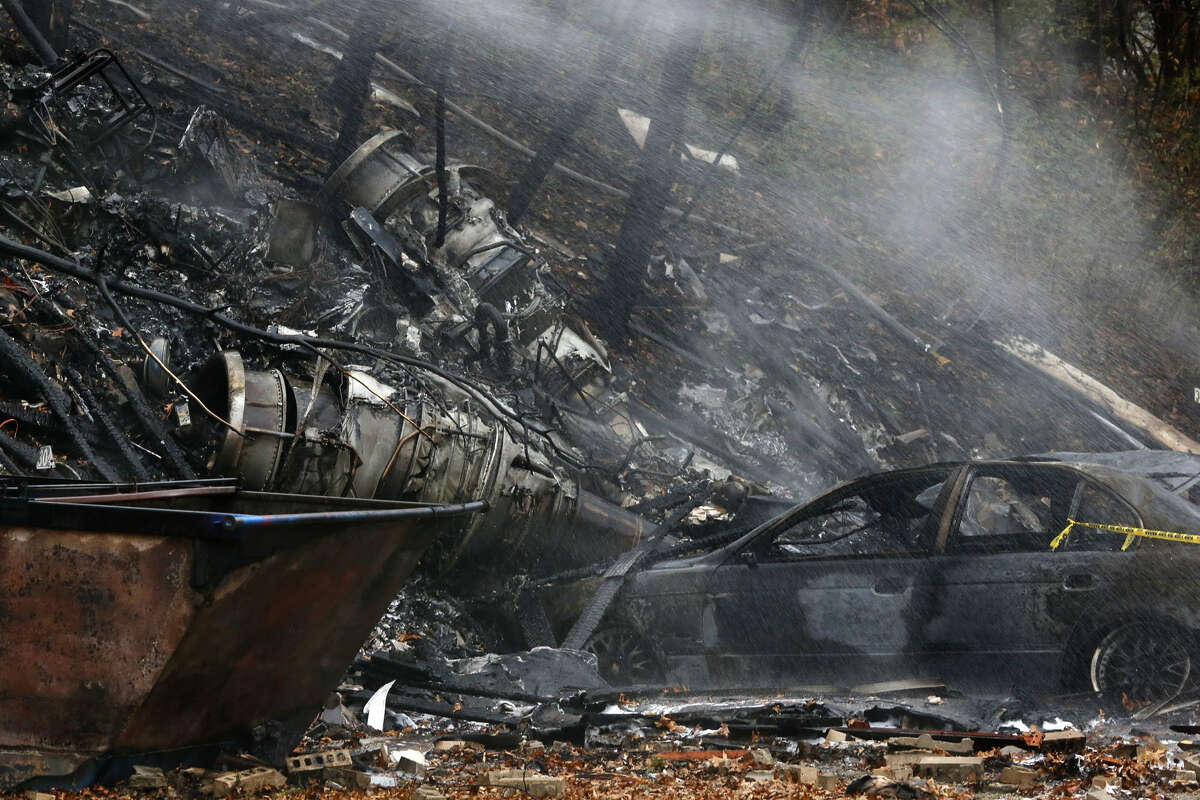 A charred car and aircraft debris smolder where authorities say a small business jet crashed into an apartment building in Akron, Ohio, Tuesday, Nov. 10, 2015. Investigators were trying to determine how many people were on the 10-seater jet, but they confirmed two deaths, said Lt. Sierjie Lash, an Akron fire department spokeswoman.