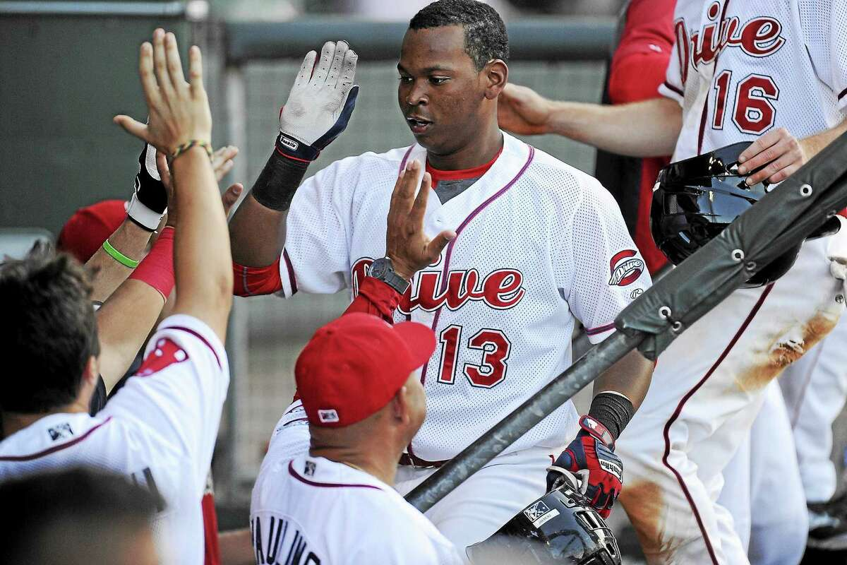 Rafael Devers (13) of the Greenville Drive is congratulated after scoring a run in a game against the Charleston RiverDogs on May 24 in Greenville, South Carolina.