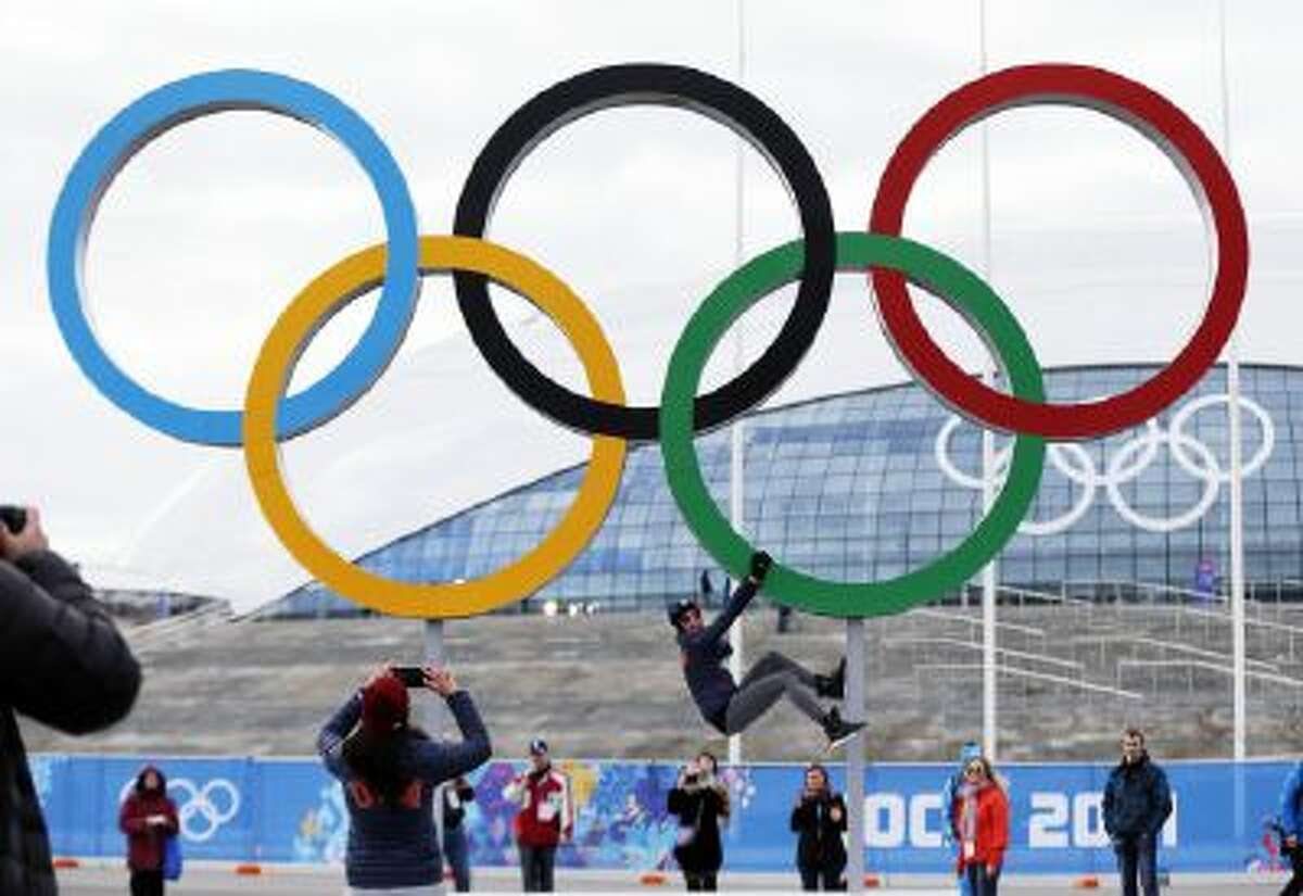 Team USA speed skater Aly Dudek of Hales Corner's, Wis., hangs from the Olympic rings while posing for a teammate at Olympic Park ahead of the 2014 Winter Olympics, Wednesday, Feb. 5, 2014, in Sochi, Russia.