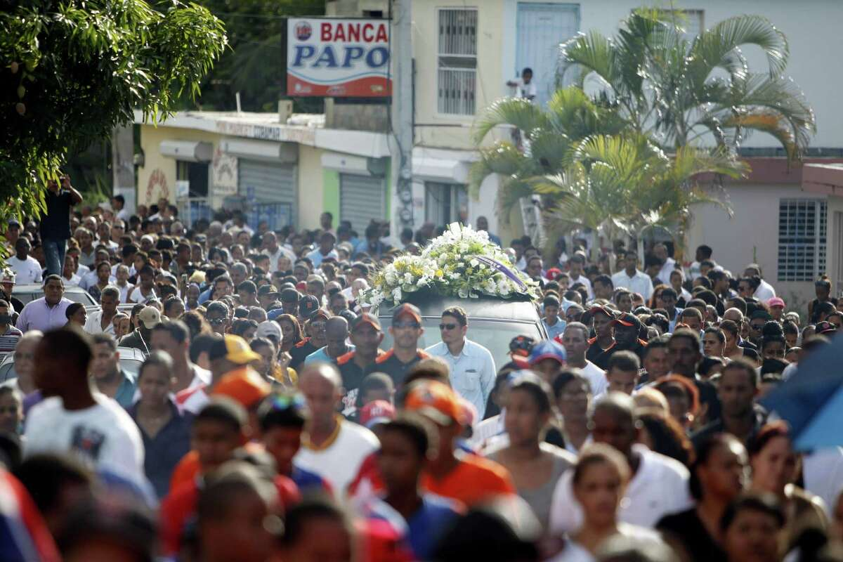 People march as a hearse carries the coffin containing the body of St. Louis Cardinals outfielder Oscar Taveras during his funeral procession on Oct. 28 in Sosua, Dominican Republic.