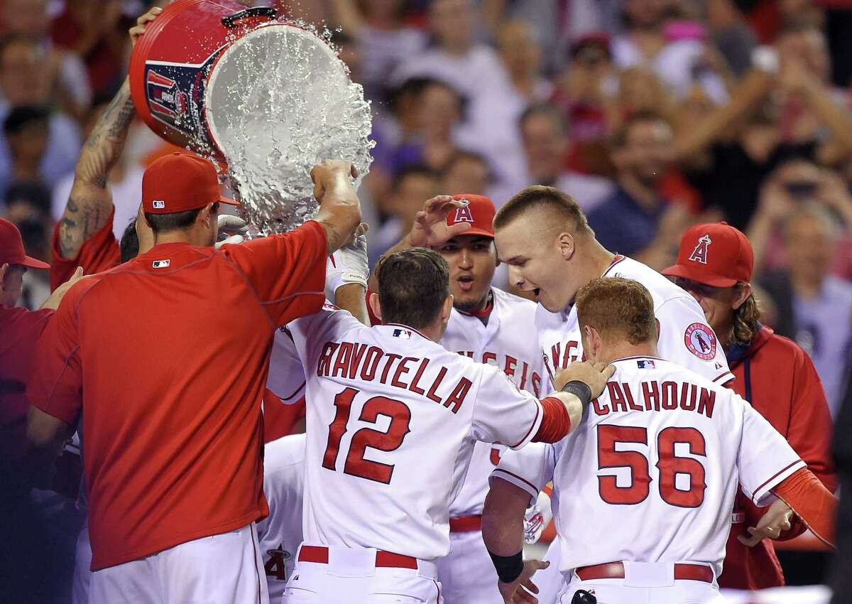 Teammates celebrate with Mike Trout as he touches home after hitting a solo home run in the bottom of the ninth inning against the Boston Red Sox in the Los Angeles Angels' 1-0 win on Friday night in Anaheim, Calif.