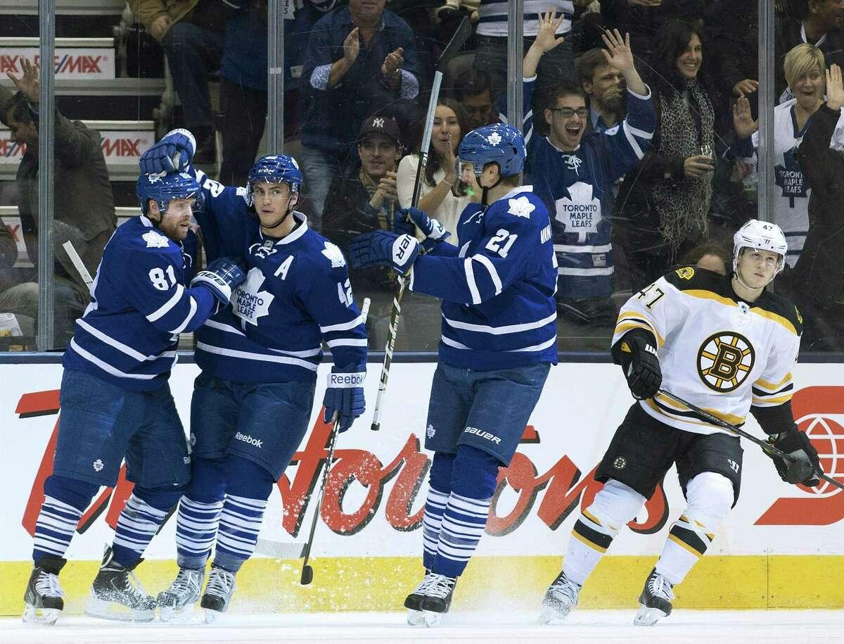 Maple Leafs forward Phil Kessel (81) celebrates his goal with teammates Tyler Bozak (42) and James van Riemsdyk (21) as Boston Bruins defenseman Torey Krug (47) skates Wednesday in Toronto.