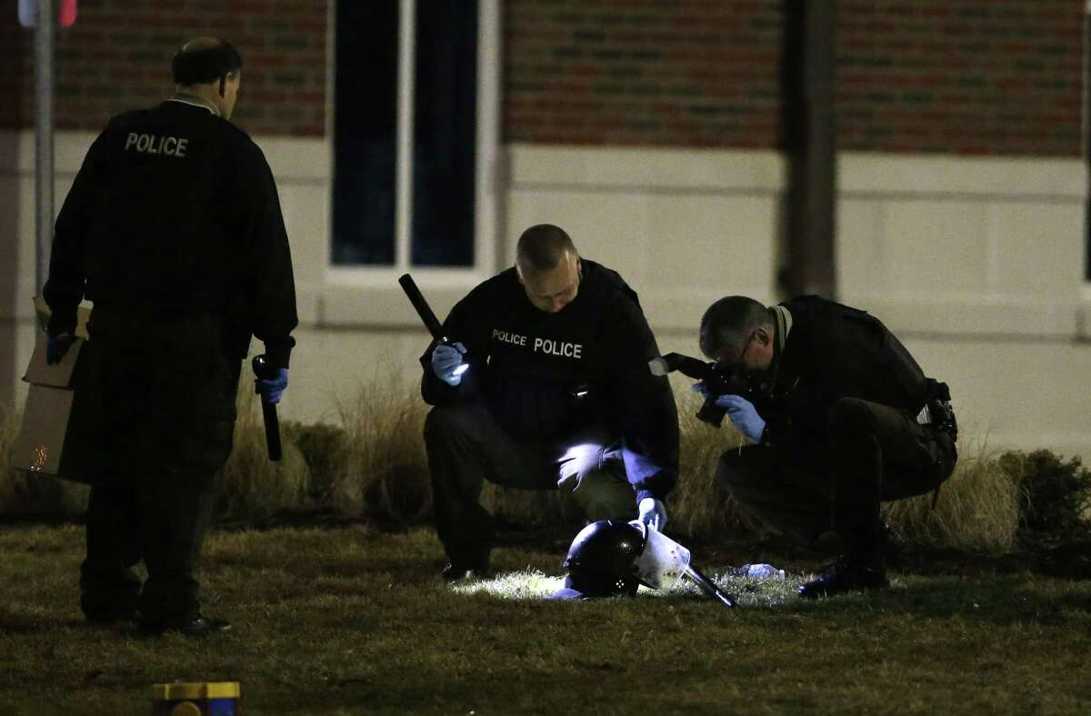 Police shine a light on and photograph a helmet as they investigate the scene where two police officers were shot outside the Ferguson Police Department on March 12, 2015, in Ferguson, Mo.