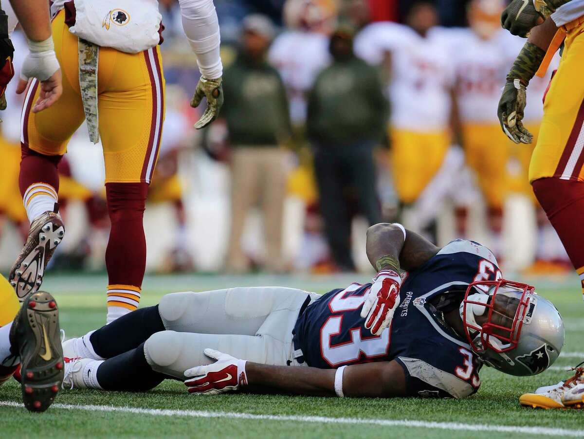 Patriots running back Dion Lewis grimaces while on the ground after being injured on Sunday.