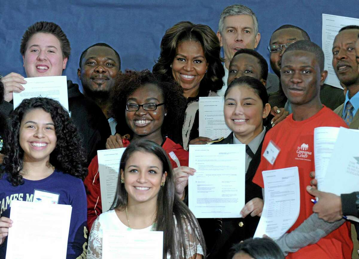 First lady Michelle Obama and Education Secretary Arne Duncan pose for a group photo with students at T.C. Williams High School in Alexandria, Va., Wednesday, Feb. 5, 2014, following a workshop to help students fill out the Free Application for Federal Student Aid. Mrs. Obama spoke to students and told them that filling out the FAFSA is a pivotal step toward finishing their education beyond high school. (AP Photo/Susan Walsh)
