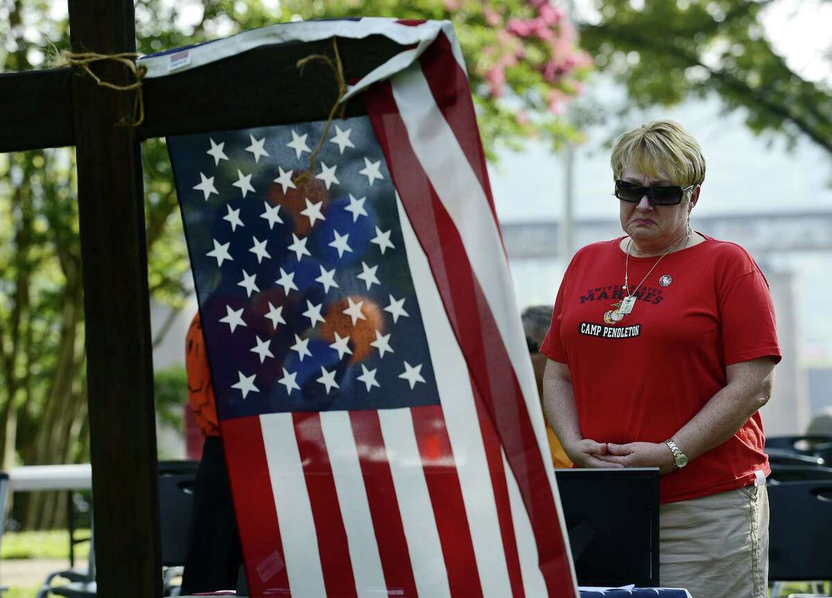 Dianna Varnes stands by a table adorned with photographs of the Marines who died after a memorial service at River Park Saturday in Chattanooga, Tenn. The U.S. Navy says a sailor who was shot in the attack on a military facility in Chattanooga has died, raising the death toll to five people.
