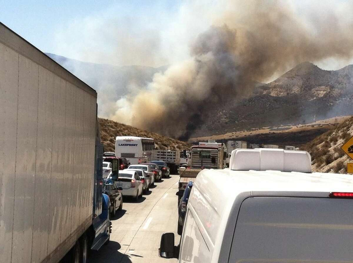 Smoke from a wildfire rises above Interstate 15 on the Cajon Pass, Friday, July 17, 2015, near San Bernadino, Calif., as a fast-moving wildfire swept across the Southern California freeway, destroying numerous vehicles and sending motorists running to safety before burning at least five homes. (Arsenio Alcantar via AP)