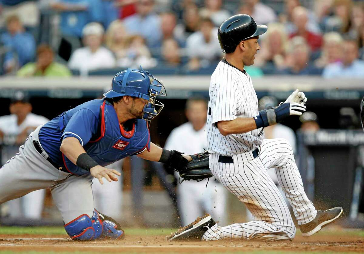 Rangers catcher Geovany Soto attempts to tag Derek Jeter, right, during Monday's game.