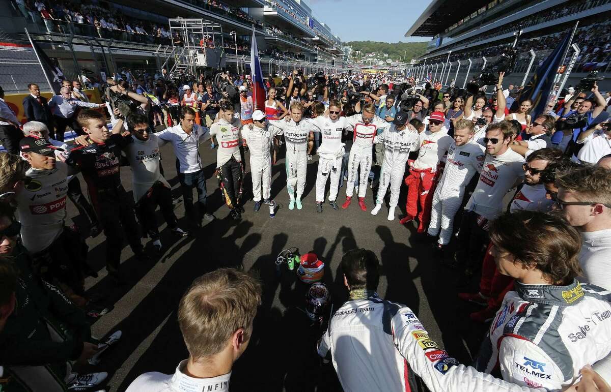 In this Oct. 12, 2014, file photo, drivers link arms to send a message of support to their injured colleague Jules Bianchi, who was fighting for his life following an accident at the Japanese Formula One Grand Prix. The family of Bianchi says the French Formula One driver has died from head injuries sustained in that crash.
