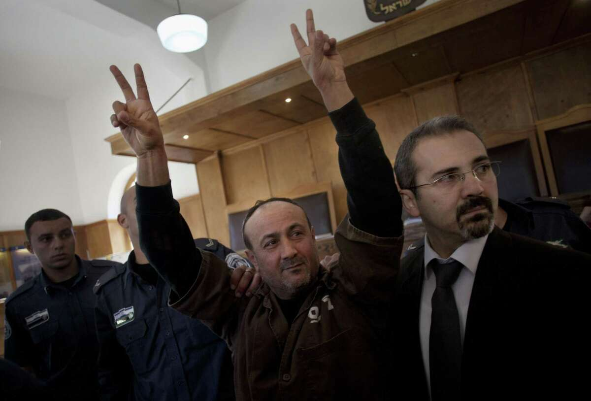 FILE - In this Wednesday, Jan. 25, 2012 file photo, senior Fatah leader Marwan Barghouti makes the victory sign in front of the media during his arrival to testify in a trial at a Jerusalem court. On Wednesday, Nov. 12, 2014, Barghouti, a Palestinian leader serving a life sentence in Israel for his role in the Palestinian uprising last decade, was sentenced to a week in solitary for calling for more violence and for the Palestinian Authority to stop its security cooperation with Israel. Israeli media interpreted that as a call for a third Intifada, or Palestinian uprising. (AP Photo/Bernat Armangue, File)