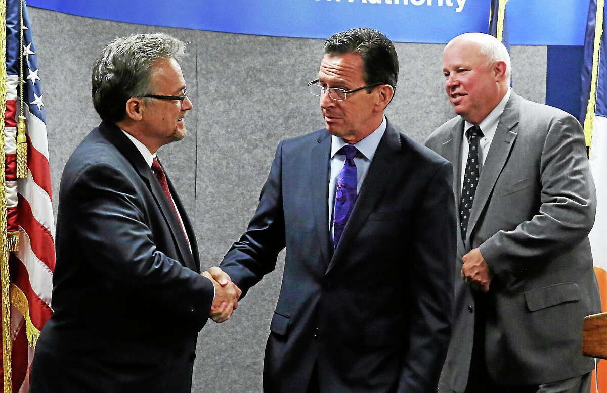 Metro-North president Joseph Giulietti, left, shakes hands with Connecticut Gov. Dannel Malloy after a news conference at MTA headquarters, in New York, Monday, June 9, 2014. MTA Chairman and CEO Thomas Prendergast is at right. Malloy and officials of the New York region's commuter transit system announced they will review detailed operations of a 118-year-old bridge over the Norwalk River, along the Metro-North Railroad, that failed twice in less than two weeks, delaying the commutes of thousands of riders into and out of New York City.