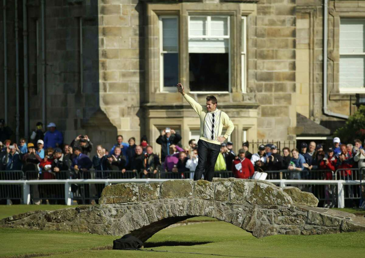 Nick Faldo waves to spectators as he stands on the Swilcan Bridge during the second round of the British Open on Friday.