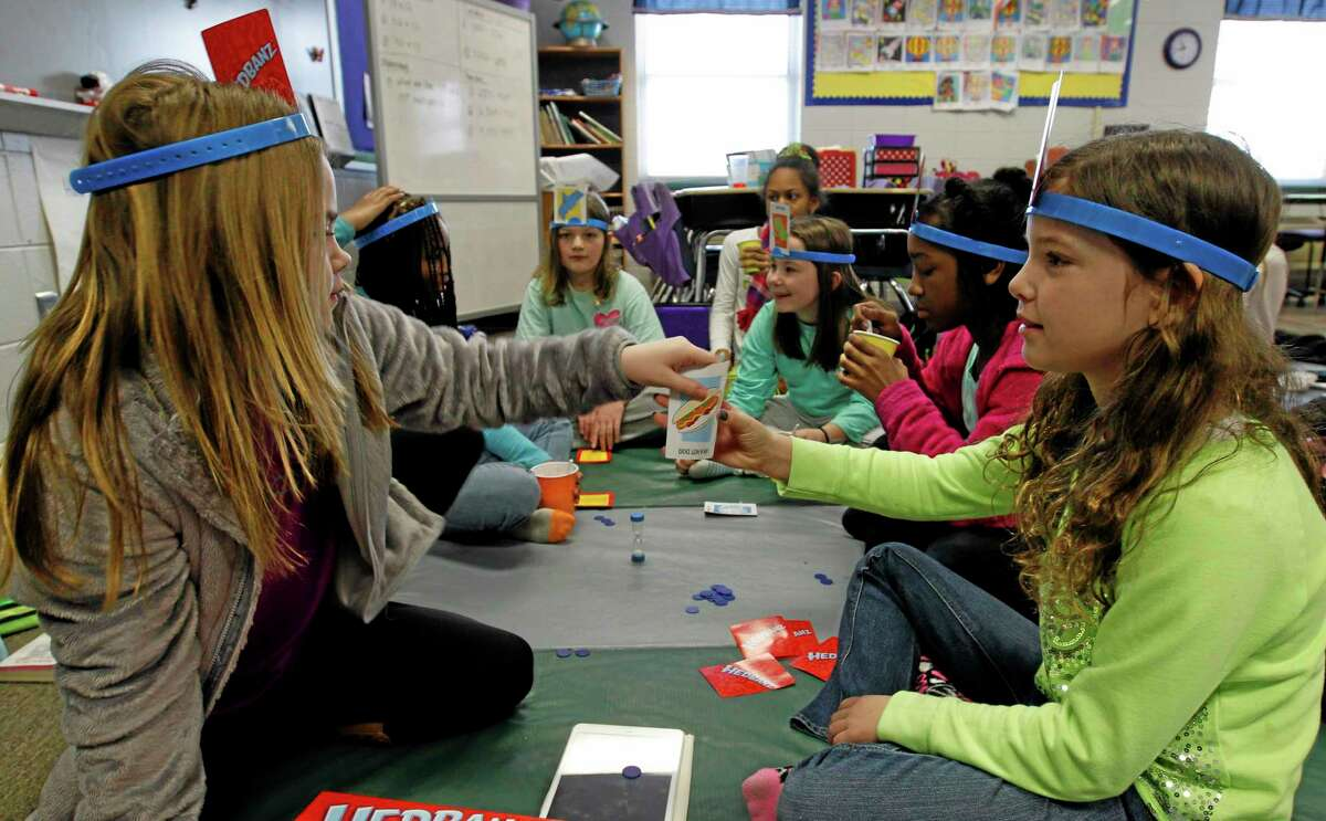 Sydney Jaffe, left, and Peyton Meadors, right, play a card game with others students at Oak Mountain Intermediate school on Wednesday, Jan. 29, 2014, in Indian Springs, Ala.