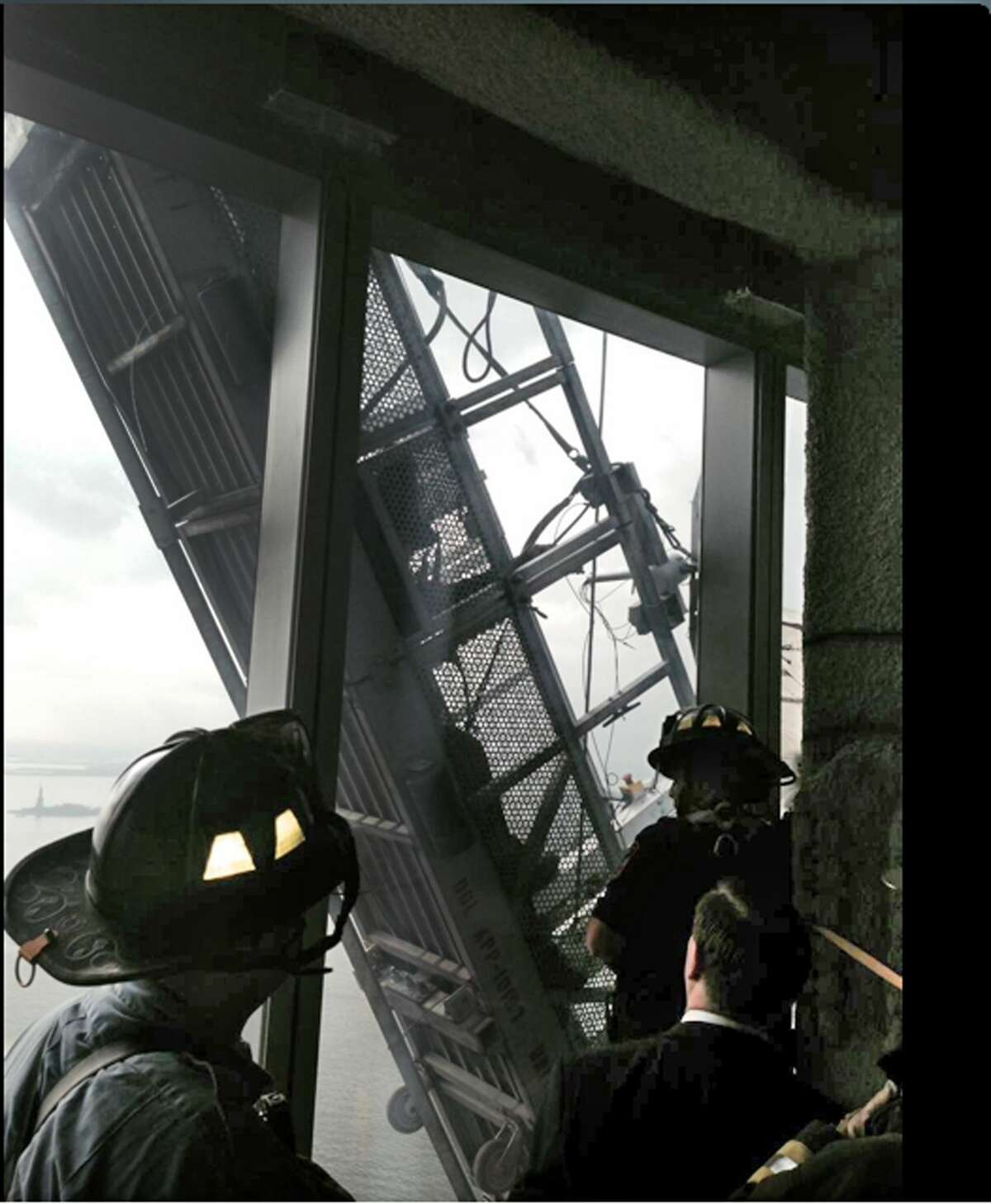"""This photo, from the Fire Dept. of New York Twitter page, shows a window washer's gondola as it hangs from 1 World Trade Center, in New York, Wednesday, Nov. 12, 2014. Two workers are stuck on scaffolding 69 stories above street level. A police official, John Miller, says the partially collapsed scaffolding is hanging at """"a 75-degree angle."""" The Fire Department said the workers are tethered and communicating with rescuers. (AP Photo/Fire Dept. of New York, Twitter)"""