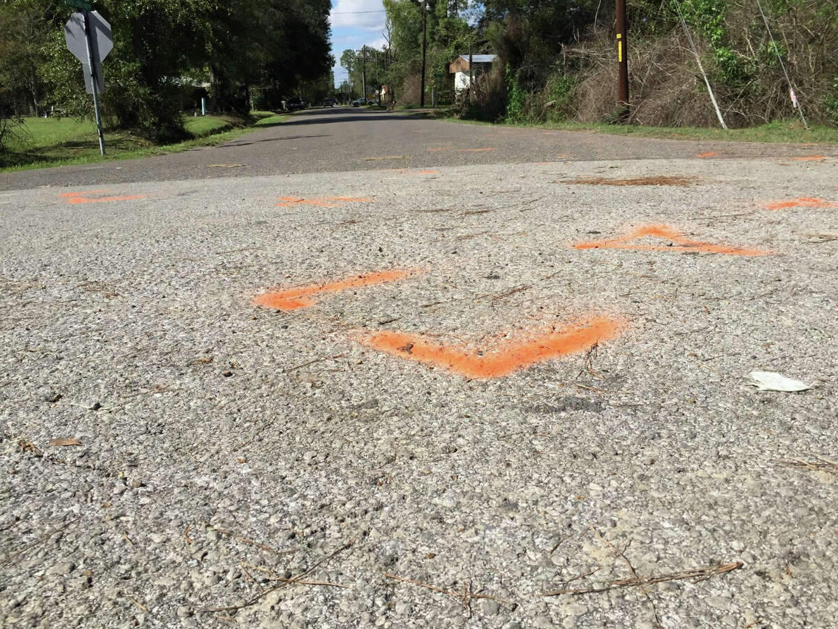 This Nov. 4, 2015 image shows orange paint marking the spot where a 6-year-old boy was shot and killed by Ward 2 city marshals in Marksville, La. The marshals had been chasing a vehicle driven by the boy's father, Chris Few. He was shot in the head, but survived.