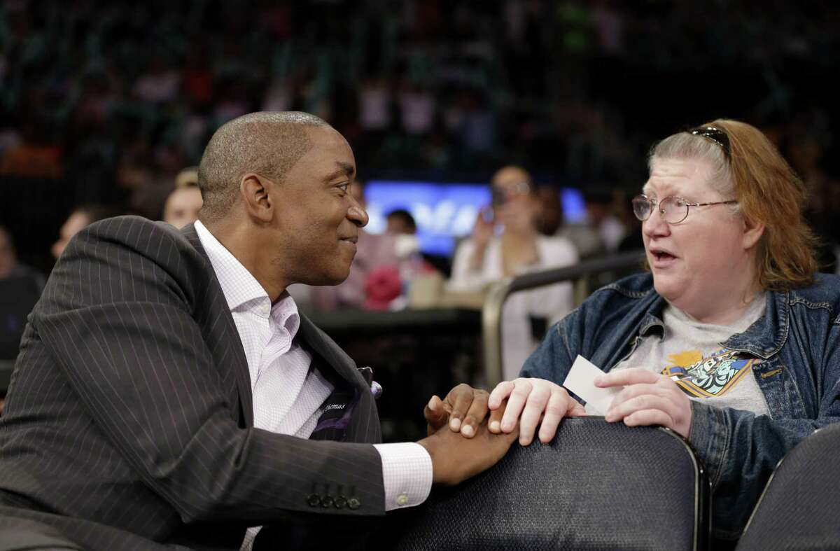 New York Liberty President Isiah Thomas, left, talks with a fan during the first half of the WNBA game between the Liberty and the San Antonio Stars in New York.