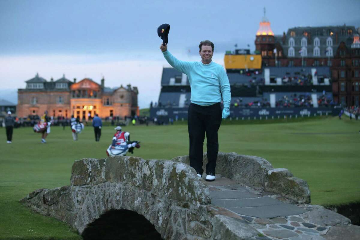 Tom Watson doffs his cap as he poses on the Swilcan Bridge for photographers during the second round of the British Open.