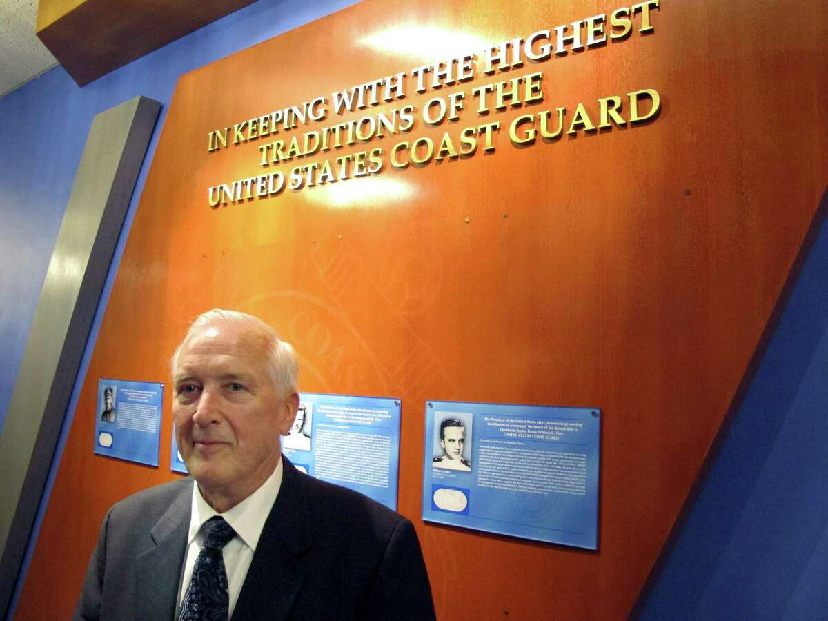 In this Nov. 6, 2015 photo, Coast Guard veteran William Carr, of Davenport, Iowa, stands in front of a plaque honoring him on the Wall of Gallantry in the Coast Guard Academy's Hall of Heroes in New London, Conn. Carr was honored at a ceremony on Friday for his heroism when he led a patrol boat crew that responded to a fire at a Navy weapons and supply base in Vietnam in 1968. He received the Bronze Star for his actions.