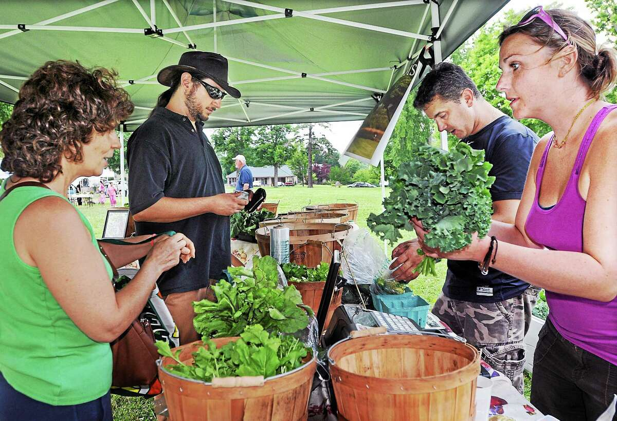 Bruno Suraci, at right owner of Tuttle Ridge Farms Organics in Durham and employee Liz Frias, at right help customers Theodora Zafiris, of Wallingford and Deep River resident Jonathan Lambert, at left buy vegetables at the Farmer's Market Thursday afternoon.
