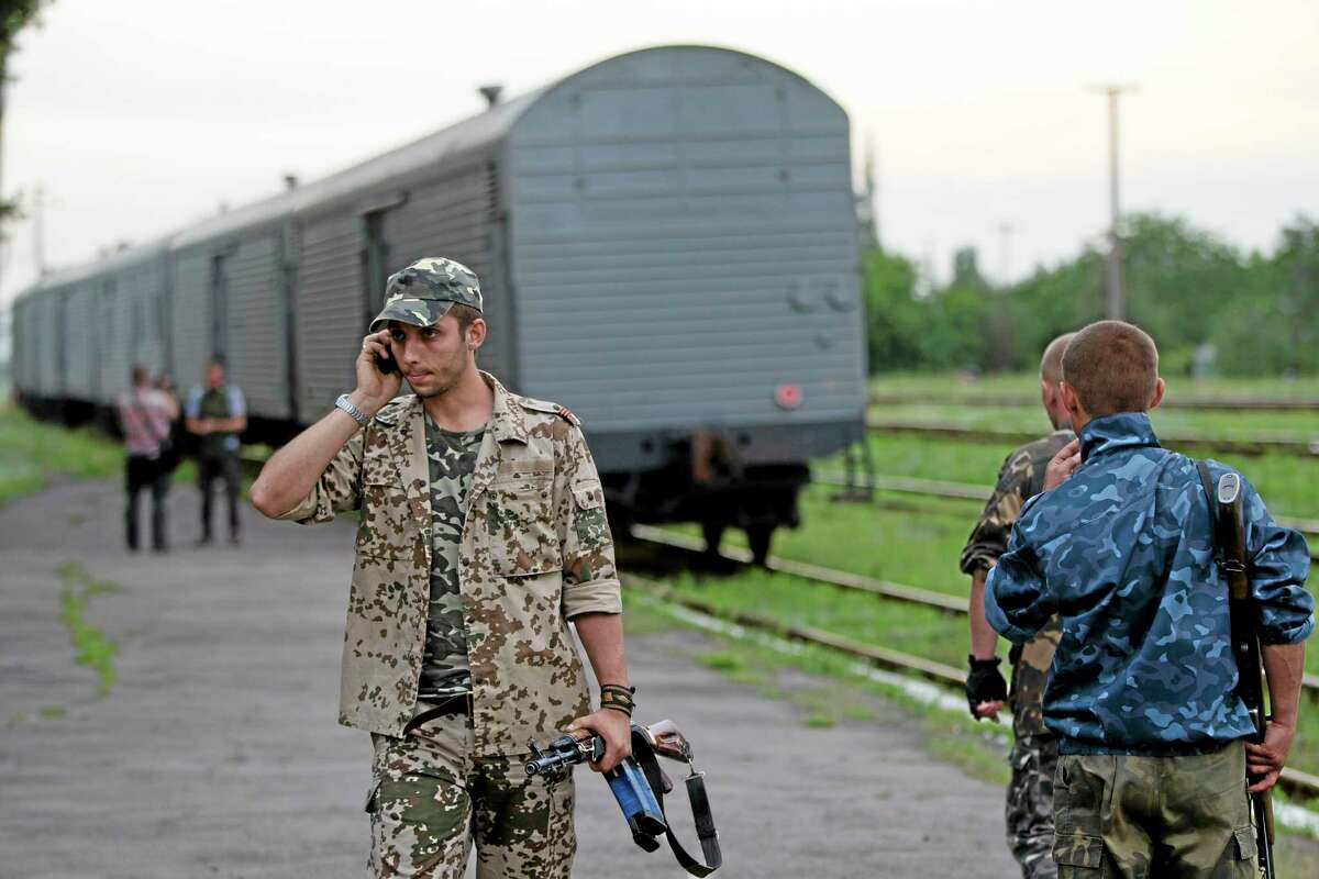 A pro-Russian rebel speaks on the phone as a refrigerated train loaded with bodies of the passengers departs the station in Torez, eastern Ukraine, 15 kilometers (9 miles) from the crash site of Malaysia Airlines Flight 17, Monday, July 21, 2014. (AP Photo/Vadim Ghirda)