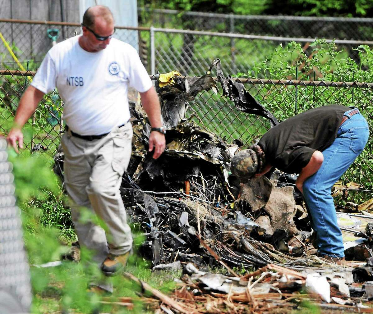 NTSB investigators and recovery team at scene Saturday August 10, 2013 of the plane crash that hit two houses Friday afternoon, August 9. 2013 at 64 and 68 Charter Oak Avenue between James and Gordon Streets in East Haven, Connecticut.
