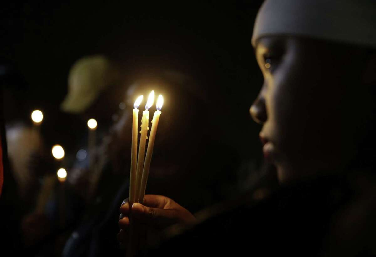 Chaunte Williams, 13, holds up three candles as she takes part in a vigil Thursday, March 12, 2015, in Ferguson, Mo. Two police officers were shot early Thursday morning in front of the Ferguson Police Department during a protest following the resignation of the city's police chief in the wake of damning U.S. Justice Department report. (AP Photo/Jeff Roberson)