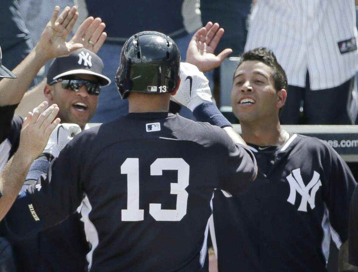 New York Yankees third baseman Alex Rodriguez (13) is greeted at the dugout steps after hitting hit his first home run of the spring off Boston Red Sox starter Brandon Workman on Wednesday in Tampa, Fla.
