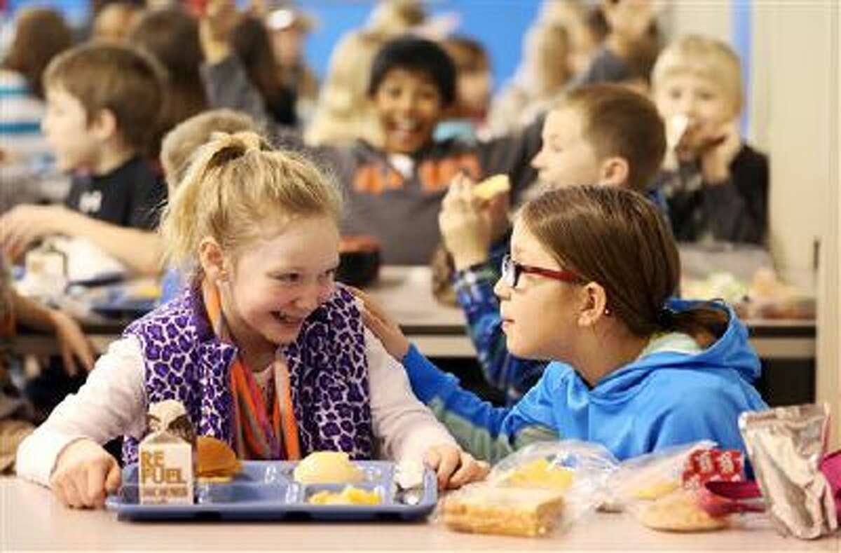 Third-graders Clare Vosberg-Padget, left, and Emily Morgan talk during lunch at Hoover Elementary School in Dubuque, Iowa.